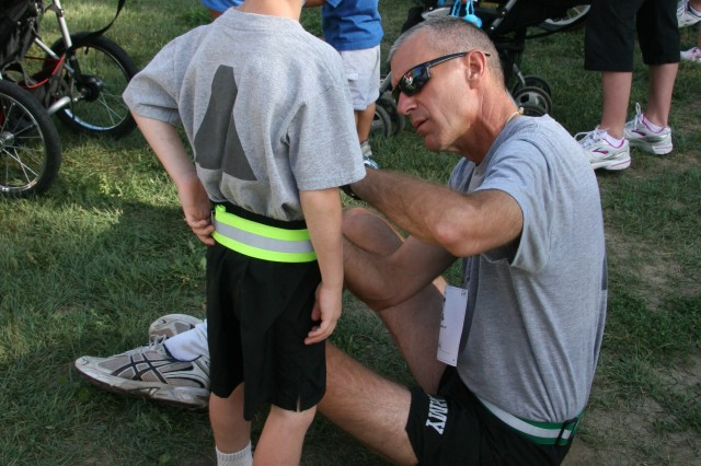 FORT CARSON, Colo.-Brig. Gen. James Pasquarette, deputy commanding general for support, 4th Infantry Division and Fort Carson, pins a bib with the name of a fallen Soldier on his son, Luke, at the Run for the Fallen.