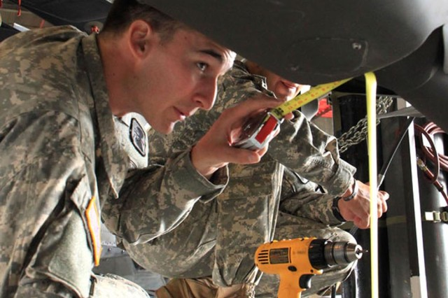 Pfc. Tyler Henson, A Company, 1st Battalion, 52nd Aviation Regiment, uses measuring tape to ensure the Blackhawk has proper clearance for transport.