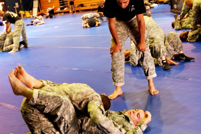 FORT HOOD, Texas -Level III certified basic instructor, Sgt. Parris Bussiere (standing), from Cape Cod, Mass., watches as Pfc. Bryant Moore (left), of Union Springs, Ala. attempts to pass the guard of Pfc. Nicholas Sawyer, from Hilsboro, Ore. at the Kieschnick Gym, here, Aug. 25