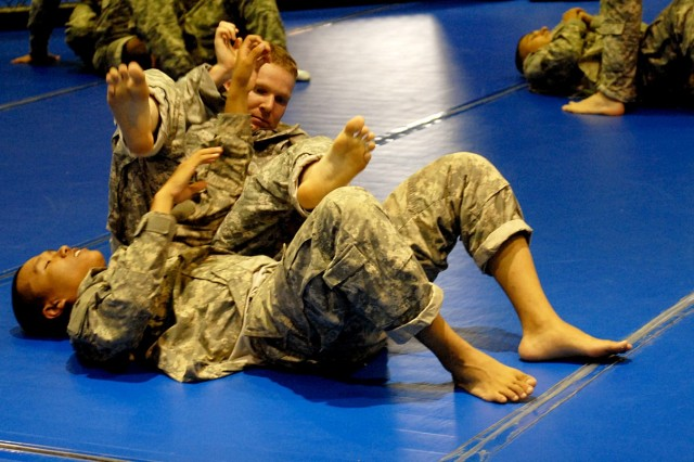 FORT HOOD, Texas -- Sgt. Bret Lowery (top), a native of Springville, Utah, practices a straight arm bar on Spc. Habakkuk Kin, of Monterrey, Calif., at Kieschnick Gym, here, Aug. 25.
