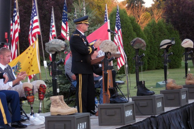"""Maj. Gen. Yves J. Fontaine, Army Sustainment Command commanding general, applauds organizers of the All-Era Veterans Healing Field event during his opening ceremony remarks Aug. 27. Speaking to some 200 guests at the Davenport, Iowa, event, Fontaine said, """"I can assure all visitors that your hearts will be touched, and that you will go away inspired and filled with a new-found appreciation for all of our veterans - past and present, living and dead - as well as for those who serve today."""""""