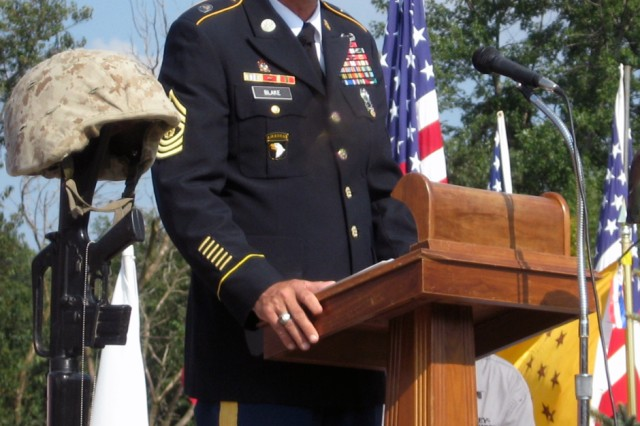 """Command Sgt. Maj. Stephen D. Blake, Army Sustainment Command, addresses the audience Aug. 29 during the closing ceremony for the Healing Field observance in Davenport, Iowa.  Speaking about the importance of remembering those who have fallen, Blake said  """"A servicemember, all of us, form a bond, stronger than a mother's love and stronger than a wedding vow."""""""
