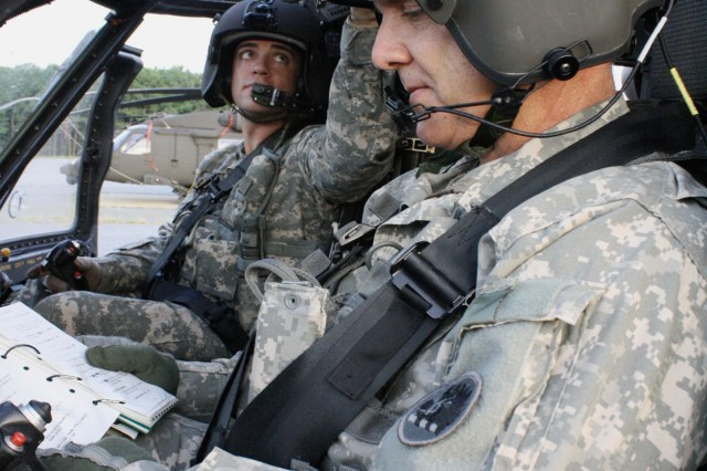 Chief Warrant Officer Gary Button reads the pre-flight checklist as his son, Warrant Officer Daniel Button, checks the gauges of the UH-60 Black Hawk helicopter.