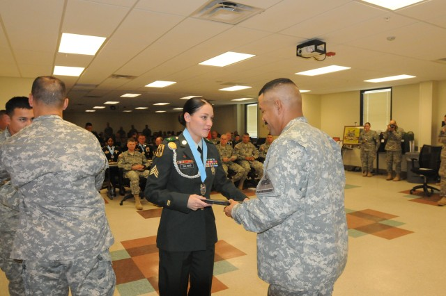 Sgt. Jennifer Crain-Salinas, 123rd Brigade Support Battalion is inducted into the Sergeant Audie Murphy club by Command Sgt. Major Phillip Pandy of the 4th Brigade, 1st Armored Division.