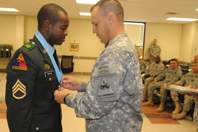 Staff Sgt. Nigel Jordan, 2nd Squadron, 13th Cavalry Regiment is inducted into the Sergeant Audie Murphy club by Col. Scott McKean, 4th Brigade, 1st Armored Division commander.
