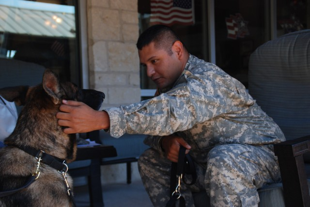 Sgt. Jesse R. Duenes, Warrior Transition Battalion, pets Anna, a 4-year-old German Shepherd, during his occupational therapy session Aug. 18. Duenes is one of several Warriors participating in a study measuring the effectiveness of animal assisted therapy using dogs.