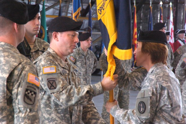 Army Air Operations Group (AAOG) Command Sgt. Maj. Chad Cuomo presents the colors to outgoing commander, Col. Jill Ludowese during the AAOG Change of Command ceremony at Davison Army air Field, Ft. Belvoir, Aug. 31.