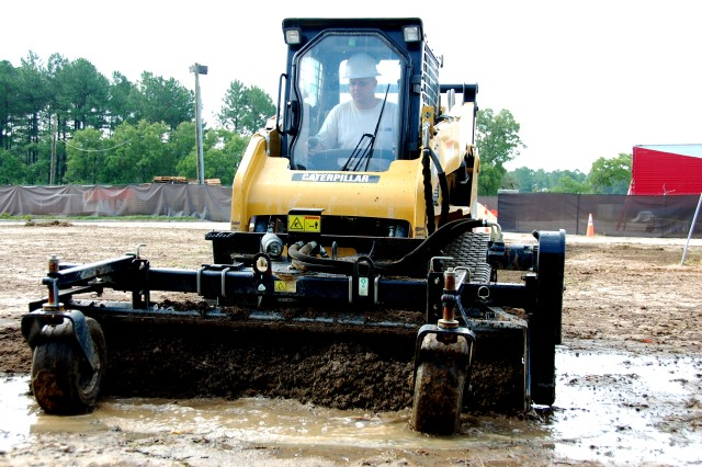 """Matt Horn, Landart Solutions, Fayetteville, NC, operates a CAT 257B Multi-terrain Loader with an attached PR184 Power Rake, August 25, 2010, to prepare the soil in front of Old Bowley School, Fort Bragg, N.C., for sod installation and seeding. Renovations converting the former elementary school to office space are underway, and the ADVON (advanced echelon) for the headquarters elements of U.S. Army Forces Command and U.S. Army Reserve Command will occupy the facility as each command relocates here from Fort McPherson, Ga., as directed by the 2005 Base Realignment and Closure Legislation. Landart Solutions is one of several small business performing work on the site, generating a positive impact on the local economy."""""""