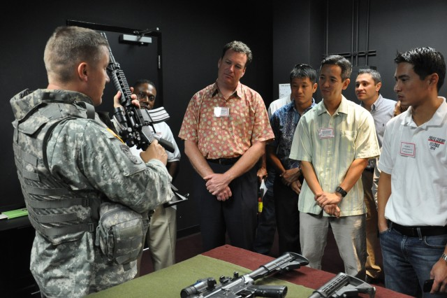 """Master Sgt. Troy Bentley, HHB, 25 ID, demonstrates the functionality of an M4 Carbine Assault Rifle instructional tool to the visiting members of the Hawaii's Pacific Century Fellows Class of 2010 during their tour of the Engagement Skills Trainer 2000 (EST 2000) at Schofield Barracks, Hawaii, Aug. 31. """"The EST 2000 is a virtual simulation tool which allows for military personnel to practice war-fighting skills through realistic combat scenarios with no effect on the environment and expenditure of resources,"""" said Sgt. Maj. Matthew McCoy, HHB, 25 ID."""