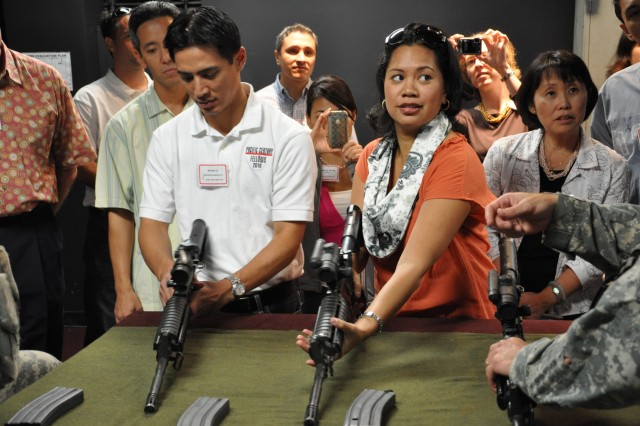"""Bryan Li (left) and Fran Gendrano, members of the Hawaii's Pacific Century Fellows Class of 2010 experience hands-on training with M4 Carbine Assault Rifle instructional tools during a tour of the Engagement Skills Trainer 2000 (EST 2000) at Schofield Barracks, Hawaii, Aug. 31. """"This is amazing,"""" said Li. """"I have a new appreciation for what Soldiers do."""""""