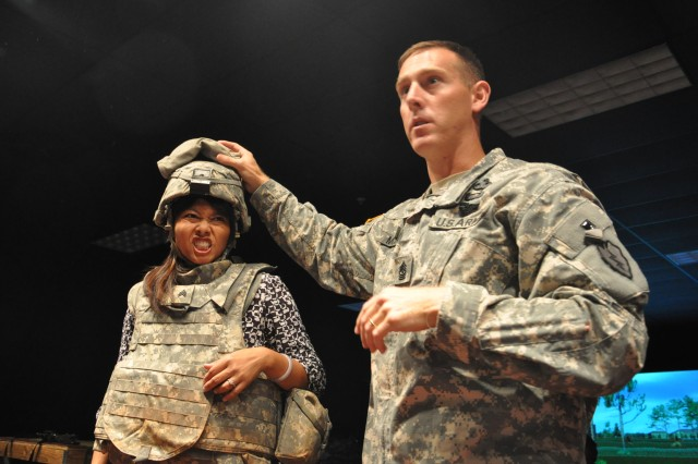 "Sgt. Maj. Matthew McCoy, HHB, 25 ID, with the help of Jen-L Lyman, a fellow participating in the tour, explains use of the Army Combat Helmet to visiting members of the Hawaii's Pacific Century Fellows Class of 2010 during their tour of the Engagement Skills Trainer 2000 (EST 2000) at Schofield Barracks, Hawaii, Aug. 31. ""The gear is awesome,"" said Lyman. ""It provides a lot of protection and safety and protection is very important for the Soldiers."""