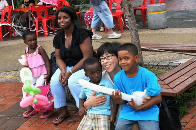 DONGDUCHEON, South Korea - Kimberly McLaurin, spouse of Sgt. Alton McLaurin, Echo Battery, 6th Battalion, 52nd Air Defense Artillery, relaxes with her children Alana (left), Alton Jr. and Jose Rouzer (far right) being hugged by a Korean visitor at the festival. The event included games, a variety of contemporary and traditional Korean folk music, and prize drawings.