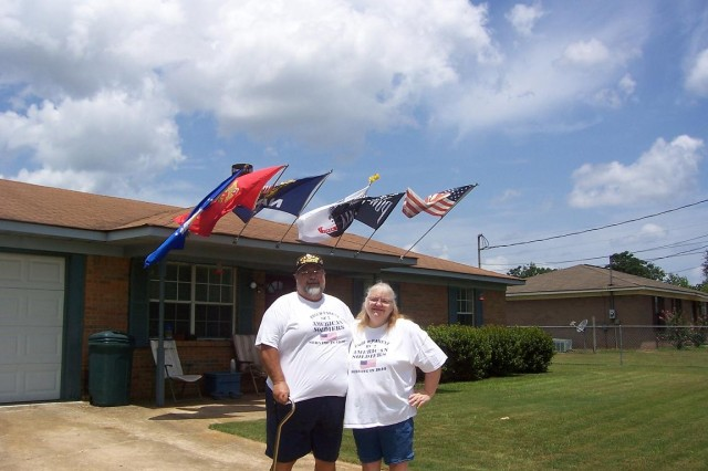 John and Vickie Harvey fly the flags of all five branches of the Armed Forces and the American flag outside their home in Midland City, Ala. John, who served in Vietnam with the Air Force, and his wife are the parents of Capt. Tanya Rosa and 1st Sgt. Greg Harvey and the grandparents of Spc. Wayne Harris.