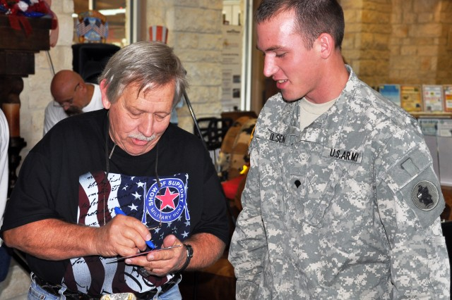 Country artist John Conlee signs a DVD for Spc. Benjamin Olsen after he and his band performed six of his hit songs at the Warrior and Family Support Center Aug. 27.