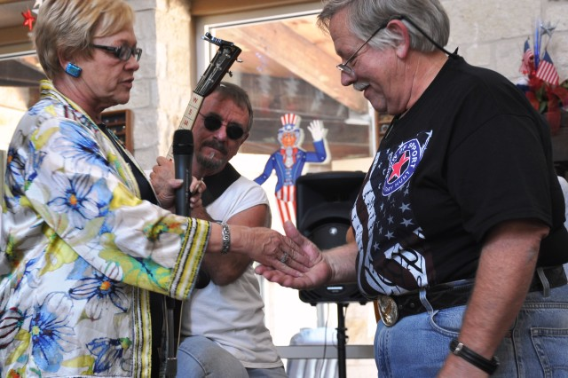 Country artist John Conlee accepts a Fort Sam Houston coin from Warrior and Family Support Center director Judith Markelz (left) after he and his band performed six of his hit songs and toured the Warrior and Family Support Center Aug. 27.