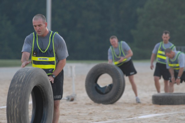 SSG Eugene Drawdy and a Team 1 teammate race to finish 25-meter laps at the Tire Flip event. Drawdy is assigned to the battalion's F Company.