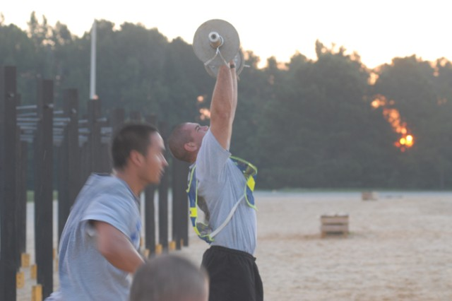 Team 2 cadre muscle their way through lifting weights for eight-minutes straight. The overall amount of weight is added up for each team's total.