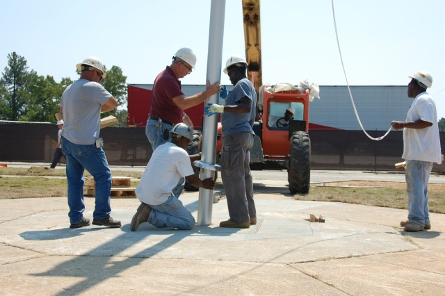 Workers with R.C. Construction Co. Inc., of Greenwood, Miss., guide a 30' flagpole into final position, Sept. 1, 2010, at Old Bowley School, Fort Bragg, N.C.  R.C. Construction is one of several small businesses working at renovating the former elementary school, which will serve as temporary office space as headquarters elements of U.S. Army Forces Command and U.S. Army Reserve Command relocate from Fort McPherson, Ga., as directed by the 2005 Base Realignment and Closure legislation.