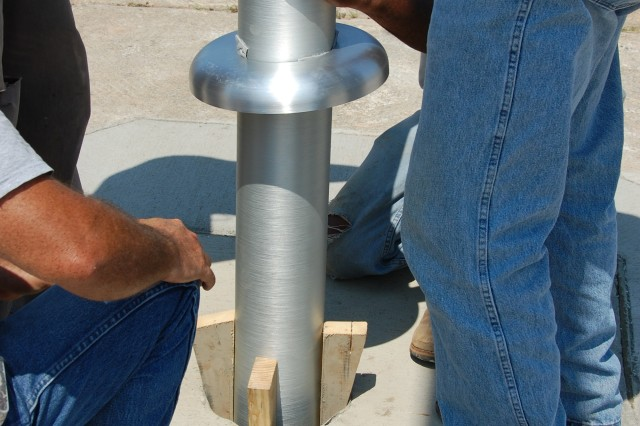 Workers use wooden shims to level a 30' flagpole in its final position, Sept. 1, 2010, at Old Bowley School, Fort Bragg, N.C.  Once the pole is in the desired position, sand will be compacted around the 4' portion of the pole which is in the shaft, anchoring it into position without the use of concrete. Old Bowley School will serve as temporary office space for headquarters elements of U.S. Army Forces Command and U.S. Army Reserve Command relocating from Fort McPherson, Ga., as directed by the 2005 Base Realignment and Closure legislation.