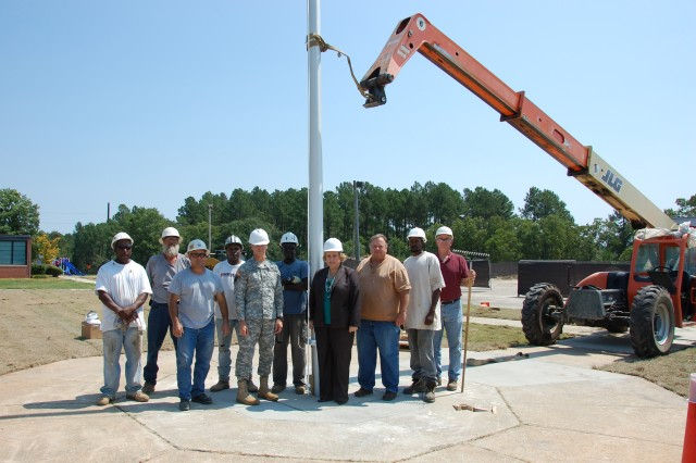 """Members of the U.S. Army Forces Command/U.S. Army Reserve Command """"Torch Party"""" and  R.C. Construction Company, Inc., of Greenwood, Miss., pose in front of a newly installed 30' flagpole, Sept. 1, 2010, at Old Bowley School, Fort Bragg, N.C.  R.C. Construction is one of several small businesses working at renovating the former elementary school, which will serve as temporary office space as headquarters elements of U.S. Army Forces Command and U.S. Army Reserve Command relocate from Fort McPherson, Ga., as directed by the 2005 Base Realignment and Closure legislation."""