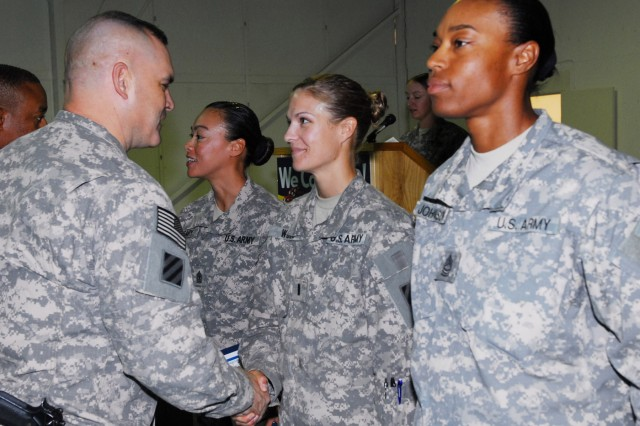 Colonel Lou Lartigue (left), commander of 4th Advise and Assist Brigade, 3rd Infantry Division, United States Division - Center, congratulates 1st Lt. Amy Gillespie, intelligence officer for Brigade Special Troops Battalion, 4th AAB, for her participation in the Vanguard Brigade's Women's Equality Day observance.