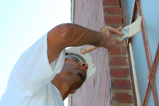 "Frank Smith, of Pembroke, N.C., a finish painter with Wish and Wash Painting Co. of Laurinburg, N.C., carefully ""cuts in"" the frame of an original window of the historic Firestone Building, Sept. 1, 2010. The building, which over the years served as an auto repair shop under various concessionaires, is now undergoing renovation to serve as temporary work space to support the relocation of the headquarters elements of U.S. Army Forces Command and U.S. Reserve Command from Fort McPherson, Ga., to Fort Bragg, N.C. Working closely  with the North Carolina State Historic Preservation Office, the U.S. Army and supporting contract firms are taking  necessary measures  to preserve the historic nature of the building."