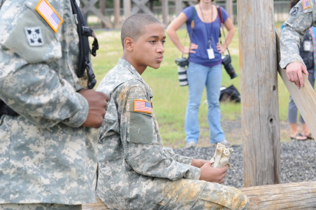 Kameon Carter, 14, takes a break after tackling the obstacle course at Range 85, Aug. 24, during the annual Teen Soldier for a Day event. Carter, a freshman at Overhills High School, attended the event along with his sister Kerstain.