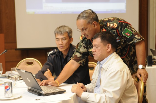 HONOLULU, Hawaii (September 1, 2010) - Lt. Gen. Pawan Jung Thapa (Nepal Army) adds his input to a presentation to prepare for his group's presentation  during  the Asia Pacific Senior Civil Military Seminar. On his right is Senior Group Captain Winyoo Jantrasoontragul (Director of the Thai Armed Forces  Academies' Medical Division) and on his left is Ronald Flores (Civil Defense Executive Officer of the Philippines' National Disaster Coordinating Council).