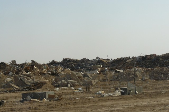 Piles of scrap metal, wood, trash and other debris at Contingency Operating Base Adder before the initial phase of the scrap metal separate and segregate mission.