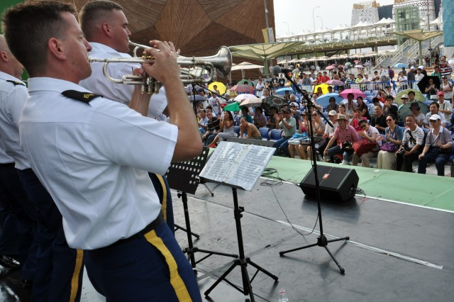 """SGT Benjamin Stevens (front) of the Tropic Lightning band blows the crowd away during a rendition of """"When the Saints Go Marching In"""", at the America Square Stage in the 2010 World Expo, Shanghai China. This particular song honored the true American heritage of Jazz and early Dixieland. Patrons clapped, danced and cheered during the energetic performance. The Division band is the first U.S. military band to perform in the World Expo and the first cultural exchange unit in China this year. The division band is in China on an international community relations mission representing the U.S. Army and Pacific Command."""