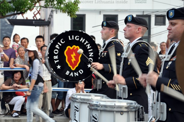 Bandsmen proudly display the Tropic Lightning emblem to the thousands of spectators lined along the streets of the 2010 World Expo in Shanghai, China. The Division band is the first U.S. military band to perform in the World Expo and the first cultural exchange unit in China this year. The division band is in China on an international community relations mission representing the U.S. Army and Pacific Command.