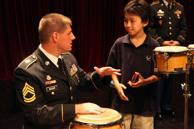 """SFC Leon Baker of the 25th Infantry Division Band answers questions about music and the U.S. Army with Shanghai Community International School, 7th grade student, Munro Azumi. """"The performance was fantastic, it was just amazing,"""" said the 12 year old marching band student Azumi. """"It was cleaner and smoother than anything I\'ve heard,"""" he added. The division band is in China on an international community relations mission representing the U.S. Army and Pacific Command. This performance was the first of this mission and is followed by multiple performances at the World Expo 2010 in Shanghai, China."""