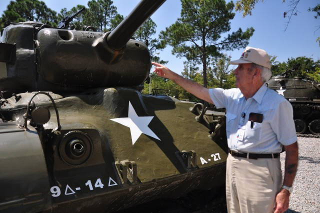 Carl Shell points to a 30-caliber machine gun on top of an M-26 Pershing Tank outside of the 120th Adjutant General Battalion (Reception) dining facility Friday. Shell was a gunner for the first and third platoons of Company A, 14th Tank battalion, 9th Armored Division during the Battle of the Bulge.