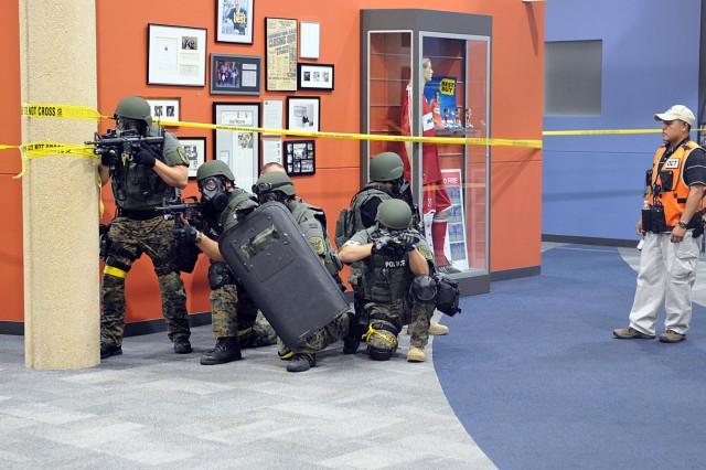 Minneapolis - Manuel Gutierrez, (Right) observer controller, CSTA, U.S. Army North, watches the Richman special weapons and tactical unit clears out notional hostiles, who unleashed a biological weapon during a simulated attack at the Best Buy Corporate Headquarters building here Aug. 25. Members of Army North's Civil Support Training Activity team, out of San Antonio, Texas, deployed to Minneapolis during the pre-evaluation training exercise in support of the 55th Civil Support Team, which was called upon by the local Richfield County police and fire department to help decontaminate a crime scene. The 55th CST is a Minnesota Army National Guard unit based out of Fort Snelling, Minn.