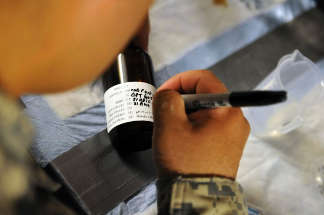 Pvt. Joseph D. Villanueva, a preventive medicine technician with Company C, 426th Brigade Support Battalion, Task Force Bastogne, labels water samples, which will be tested for harmful chemicals at Forward Operating Base Fenty, Aug. 31.