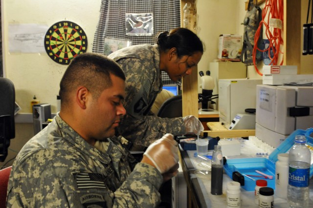 Pvt. Joseph D. Villanueva, a preventive medicine technician and Capt., Susan N. Gosine, the preventive medicine officer in charge, prepare to test water samples for harmful chemicals at Forward Operating Base Fenty Aug. 31. Both Soldiers are assigned to Company C, 426th Brigade Support Battalion, Task Force Bastogne.