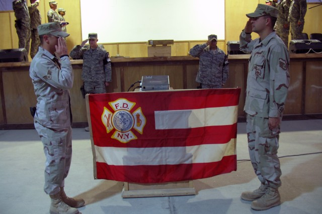 Soldiers and Airmen honor a New York Fire Department Flag that flew at Ground Zero during 1st Platoon, 962nd Ordnance Company Transfer of Authority Ceremony Jan. 6, 2009. (U.S. Army photo Sgt. Heather Wright)