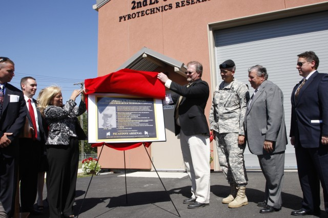 Shawn Wroblewski, mother of 2nd Lt. John Thomas Wroblewski, and James L. Wejsa, chief of the Pyrotechnics Technology and Prototyping Division here, unveil a replica of the plaque that will welcome visitors to the new pyrotechnics complex. At the new complex, dedicated in the fallen Marine's honor, Picatinny scientists and engineers will develop items such as delay mechanisms for hand grenades and fuzes, expulsion charges for payload munitions, Soldier signaling devices, and training simulators.
