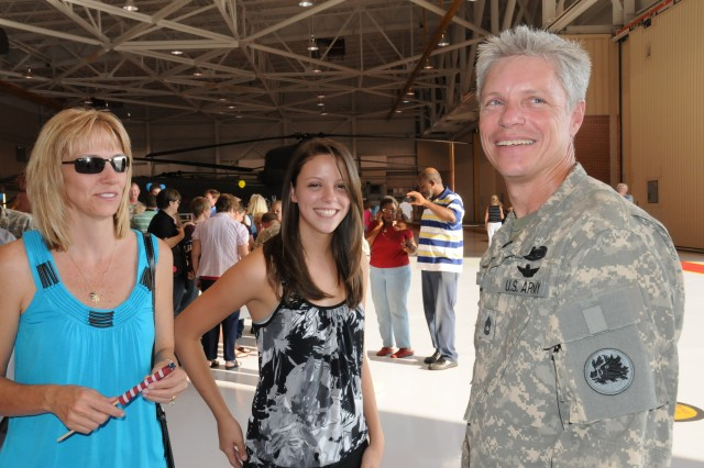 Sergeant First Class Richard Sparks, 1/169 Aviation, re-unites with his wife, Tracey and daughter Kristen at the homecoming ceremony at the National Guard hanger on Hunter Army Airfield, Sept. 3.