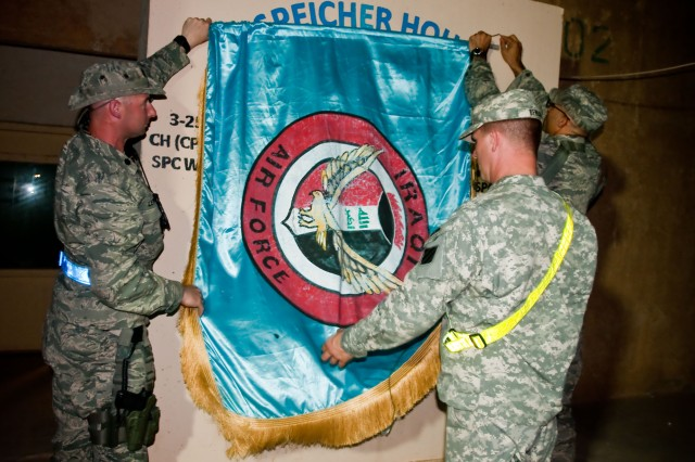 Two U.S. Airmen and a U.S. Soldier hang the Iraqi Air Force colors at Contingency Operating Base Speicher, Iraq, Sept. 1. The colors were hung to welcome 157 Iraqi Air Force cadets to the Iraqi Air Force Academy, which was recently re-opened on COB Speicher after being closed for seven years.