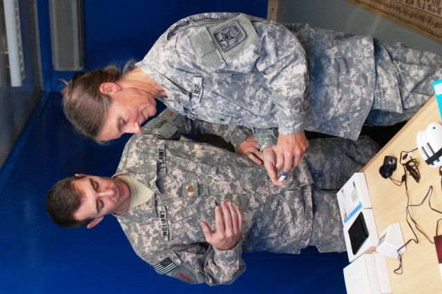 Maj. Scott Williams, left, from the 1st Infantry Division surgeon's office talks Brig. Gen. Rhonda Cornum, director of Comprehensive Soldier Fitness, through the use of a bio-scanner at the bio-feedback room of the Basra Resiliency Center Sept. 9. The center is open to all service members, providing support for the Five Pillars of Comprehensive Soldier Fitness. (Army Photo by Sgt. Cody Harding, 1st Inf. Div. Public Affairs.)