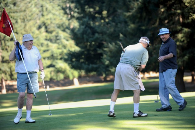 Chuck Aly, left, George Baird, and Don Rogers are all grins after making puts on the blue course's eighth green at Eagles Pride Golf Course, Aug. 25.