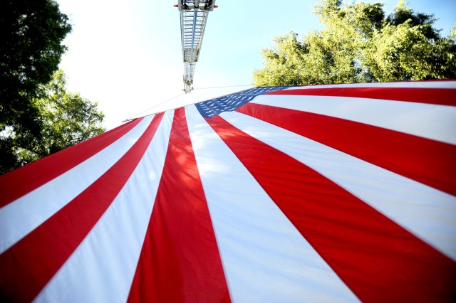 A giant American flag provides a patriotic backdrop at Puyallup's Pioneer Park for a new monument dedicated to the memory of the 37 soldiers from 5th Bde., 2nd Inf. Div. killed while serving in Afghanistan.