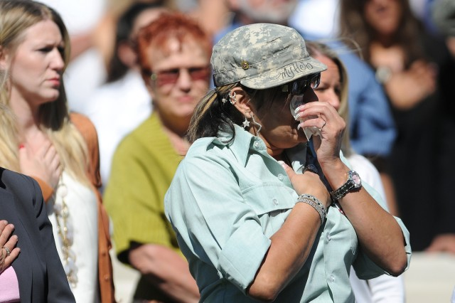Patricia Dahl, the mother of Spc. Michael Dahl, wipes tears from her eyes during the playing of the national anthem at a ceremony Sept. 2 at Puyallup's Pioneer Park in honor of the 37 soldiers from 5th Bde., 2nd Inf. Div. killed while serving in Afghanistan.