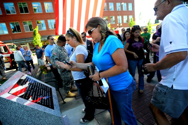 Allysha Dennis, center, photographs a monument at Puyallup's Pioneer Park Sept. 2 in memory of the 37 soldiers from 5th Bde., 2nd Inf. Div. killed while serving in Afghanistan. Dennis' husband, Pfc. Jacob Dennis, was killed 15 days before he was scheduled to return home.