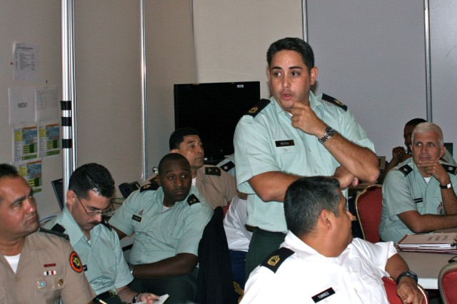 Sgt. 1st Class Javier Rosa, U.S. Army South operations sergeant, conducts a shift change briefing that includes seven Partner Nation soldiers during Panamax in Panama City, Panama Aug. 26.  Rosa was the noncommissioned officer in charge over the Joint Operations Center.  Panamax is a multinational maritime exercise focused on Panama Canal Zone security.  18 countries providing over 2,000 personnel participated in this year's exercise.  (U.S. Army Photo By:  Lt. Col. McKinley Williams, U.S. Army South) /RELEASED