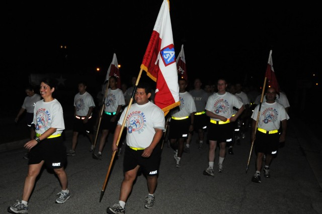 FORT SAM HOUSTON, Texas - Lt. Col.  Shannon Miller (left), commander, Headquarters and Headquarters Battalion, U.S. Army North, and Sgt. 1st Class Barney Muller, color bearer, lead a procession of Army North Soldiers, Civilians and Family members during Fort Sam Houston's inaugural Freedom Walk to remember the victims of 9/11 and to honor the nation's service members in the pre-dawn hours Sept. 10 here at the historic Quadrangle. Army North is the Army Service Component Command and Joint Force Land Component Command to U.S. Northern Command. It conducts homeland defense, civil support operations and theater security cooperation activities in order to protect the American people and our way of life.