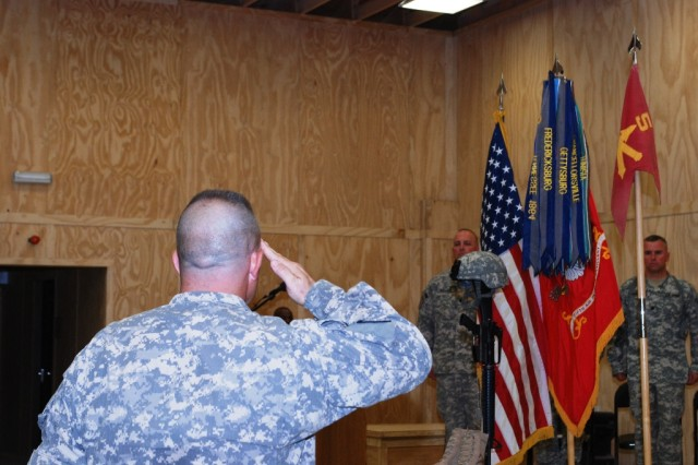 First Sgt. Billy Lingar, the Battery A, 5th Battalion, 5th Air Defense Artillery Regiment senior noncommissioned officer, salutes the memorial to Sgt. Brandon Maggart after the 'Last Role Call' during a ceremony at the Contingency Operating Base Basra chapel Aug. 26. The Last Role Call, followed by a 21-gun salute, is an expression of honor for Soldiers who fell in service to the country.