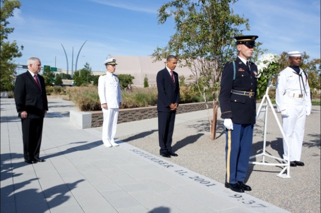 President Barack Obama, flanked by Defense Secretary Robert Gates and Joint Chiefs Chairman Adm. Michael Mullen, bows his head after laying a wreath at the Pentagon, Sept, 11, 2010.