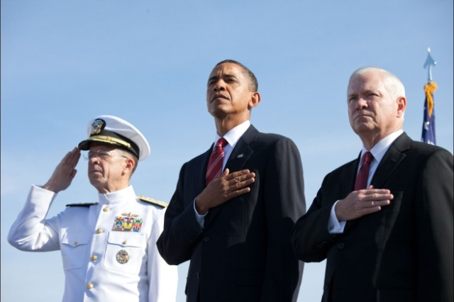 President Barack Obama, standing with Defense Secretary Robert Gates and Joint Chiefs Chairman Adm. Michael Mullen, listens to the national anthem during a ceremony marking the events of September 11th at the Pentagon, Sept. 11, 2010.